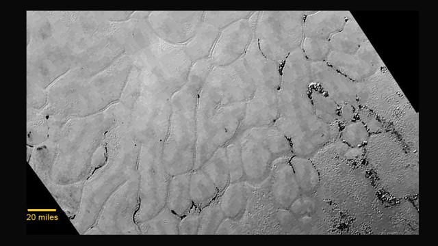 "In the center left of Pluto's vast heart-shaped feature – informally named ""Tombaugh Regio"" - lies a vast, craterless plain that appears to be no more than 100 million years old, and is possibly still being shaped by geologic processes. This frozen region is north of Pluto's icy mountains and has been informally named Sputnik Planum (Sputnik Plain), after Earth's first artificial satellite. The surface appears to be divided into irregularly-shaped segments that are ringed by narrow troughs. Features that appear to be groups of mounds and fields of small pits are also visible. This image was acquired by the Long Range Reconnaissance Imager (LORRI) on July 14 from a distance of 48,000 miles (77,000 kilometers). Features as small as one-half mile (1 kilometer) across are visible. The blocky appearance of some features is due to compression of the image. Credits: NASA/JHUAPL/SWRI"